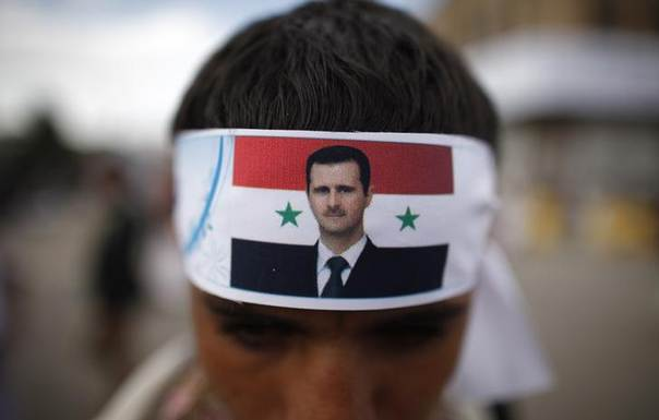 A protester loyal to the Shi'ite Muslim Al-Houthi group, also known as Ansarullah, wears a headband with a picture of Syria's President Bashar al-Assad as he attends a demonstration against potential strikes on the Syrian government, in Sanaa September 6, 2013. REUTERS/Khaled Abdullah