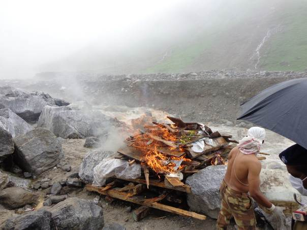 A solider from the Indian army puts wood on a funeral pyre during the mass cremation of bodies recovered in the aftermath of floods in the holy town of Kedarnath in India's northern Uttarakhand region on July 5, 2013. Photo by Air Commodore Rajesh Isser/Indian Air Force