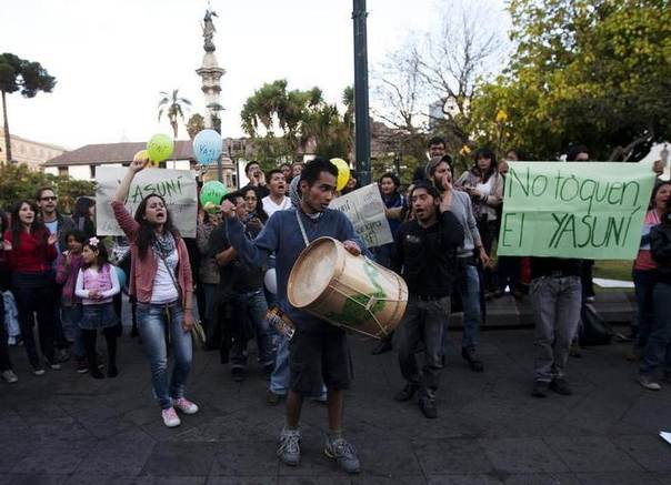 Demonstrators shout slogans during a rally calling for the government to keep the Yasuni initiative in place, outside Carondelet Palace in Quito. The sign reads,