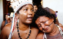Preta (L) and Gabao from Brazil's indigenous Gamela tribe react after members of their tribe were injured in a dispute over land in northern Brazil