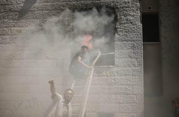 Palestinians react as they help to put out a fire in an apartment which witnesses said was hit by an Israeli air strike in Beit Lahiya in the northern Gaza Strip August 10, 2014. REUTERS/Mohammed Salem