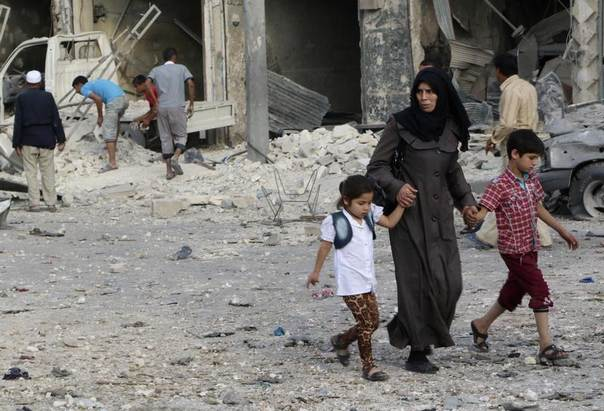 A Syrian woman with her children flee a site hit by what activists said was a bomb dropped by government forces, Aleppo, June 8, 2014. REUTERS/Mahmoud Hebbo