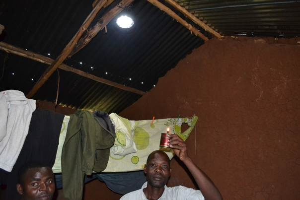 Timothy Nyongesa compares the light from a kerosene tin lamp with that from an IndiGo solar lamp, hanging in his home. THOMSON REUTERS FOUNDATION/Isaiah Esipisu