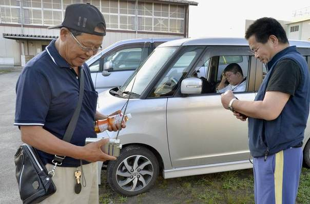 Local residents listen to radio broadcasts to gather information upon escaping to an elementary school after a tsunami warning was issued in Sendai, in this photo taken by Kyodo July 12, 2014 REUTERS/Kyodo