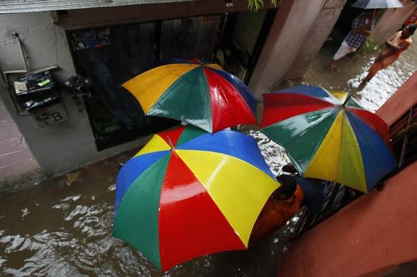 A group of people hide from the rain under umbrellas on a flooded street in a small residential area in Colombo, Sri Lanka, May 17, 2010. REUTERS/Andrew Caballero-Reynolds