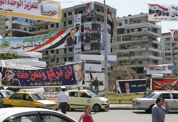 Election posters of Syria's President Bashar al-Assad hang along a street and on buildings in Latakia city May 24, 2014. REUTERS/Khaled al-Hariri