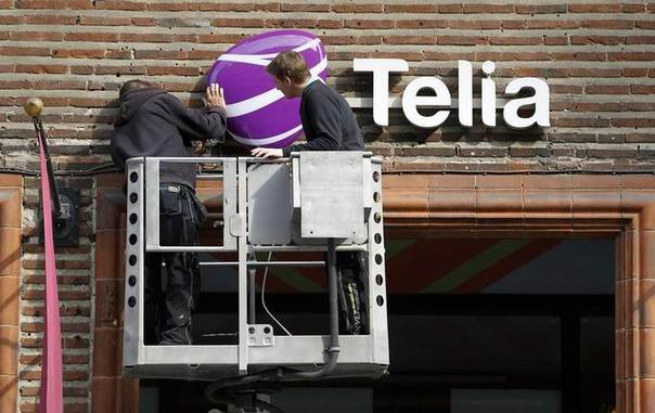 In this 2011 file photo, workmen install a sign with TeliaSonera's new corporate logo, outside a store in downtown Stockholm REUTERS/Bob Strong