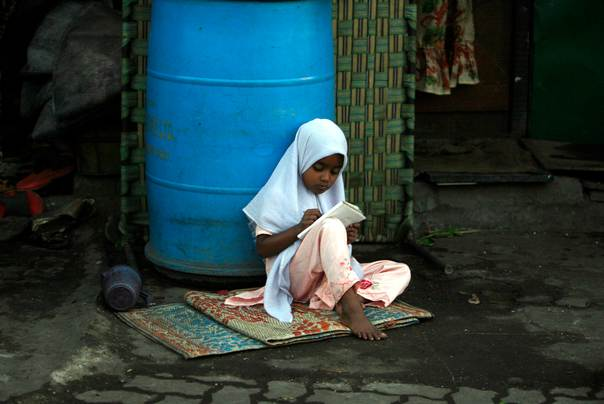 A girl writes in a book as she sits in front of her shanty at a slum in Mumbai, on Feb. 27, 2009. REUTERS/Arko Datta