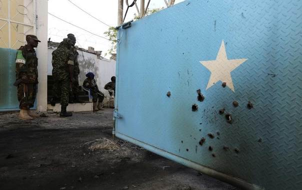 Soldiers serving in the African Union Mission in Somalia (AMISOM) assess the damage sustained during an attack at the presidential palace in the capital Mogadishu July 9, 2014. REUTERS/Feisal Omar
