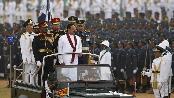 Sri Lanka's President Mahinda Rajapaksa (in white) inspects a parade during the War Victory parade, in Colombo, May 18, 2013. Sri Lanka held a military parade and memorial for fallen soldiers to mark the fourth anniversary of the defeat of the Tamil Tigers, which ended a quarter-century civil war in the Indian Ocean nation. REUTERS/Dinuka Liyanawatte