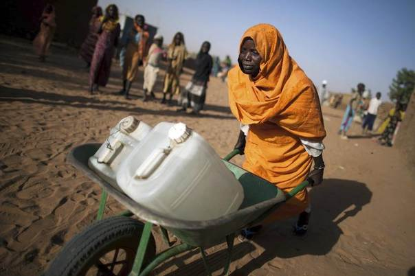 Kariya Mohamed Abbakar, 50, from Jebel Saiey, North Darfur, pushes a wheelbarrow loaded with jerrycans of water as she returns to her shelter from the nearest waterpoint at the Abu Shouk camp for displaced people in El Fasher, March 19, 2013. REUTERS/Albert Gonzalez Farran/UNAMID/Handout