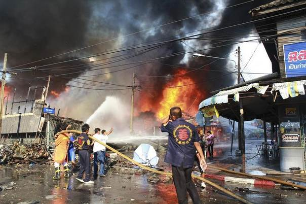 Rescue workers extinguish a fire at the site of a bomb blast in southern Thailand's Yala province, April 6, 2014. REUTERS/Stringer