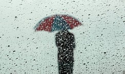 A man carrying an umbrella is seen silhouetted through a window covered with rain drops during a wet day in Colombo