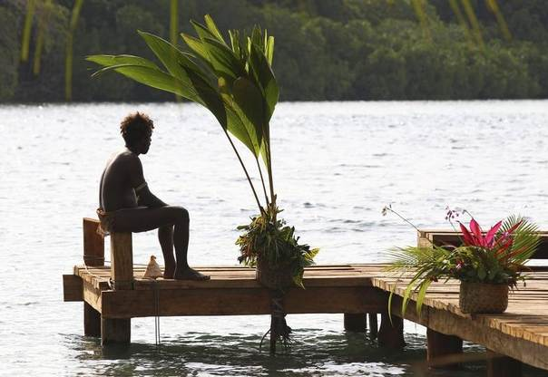 A man from a village waits to blow a conch shell at a jetty in Marapa Island, Solomon Islands, Sept. 17, 2012. REUTERS/Rick Rycroft/Pool