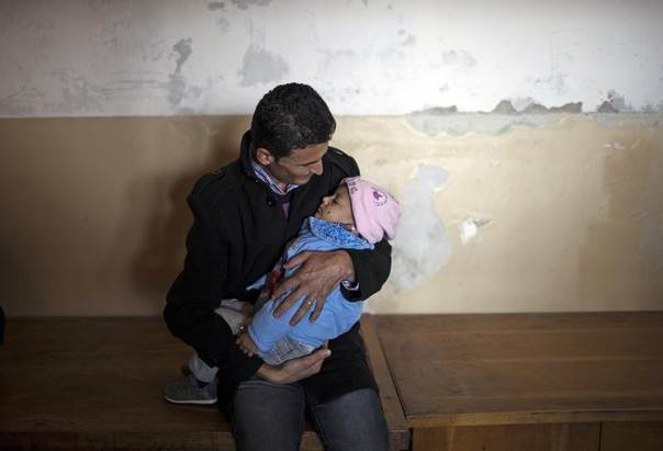 A Syrian man holds his child as he waits for medical supplies at a recently opened shelter in Vrazhdebna, near Sofia December 3, 2013. REUTERS/Pierre Marsaut