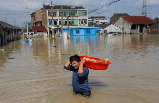 A man carries his belongings in a basin as he walks in a flooded street in Yuyao, in China's Zhejiang province, on October 10, 2013. REUTERS/China Daily
