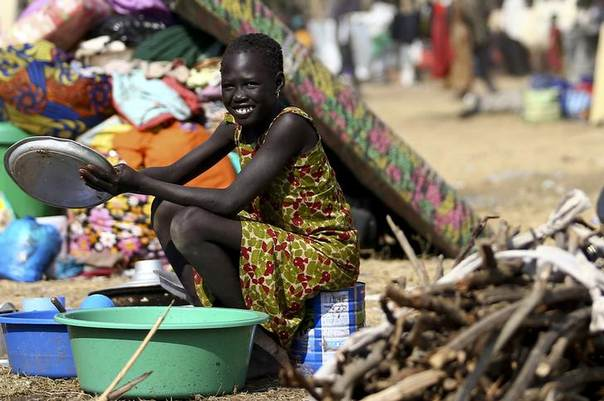 A South Sudanese refugee girl washes utensils at the Tzaipi refugee camp in Adjumani, 470 km north of Uganda's capital Kampala. Picture January 17, 2014, REUTERS/Edward Echwalu