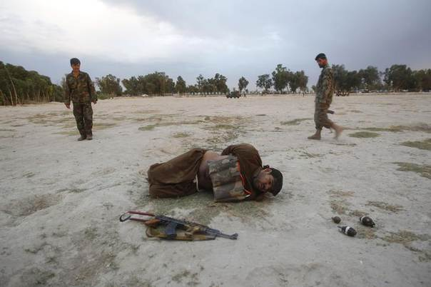 Afghan National Army (ANA) soldiers approach a suicide attacker after his vest was defused in Jalalabad province June 30, 2013 REUTERS/Parwiz