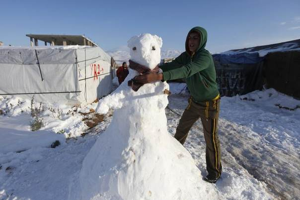 A Syrian refugee from the northern province of Raqqa places a scarf around a snowman in a Syrian refugee camp beside the Lebanese border town of Arsal, in eastern Bekaa Valley December 12, 2013.REUTERS/Alia Haju