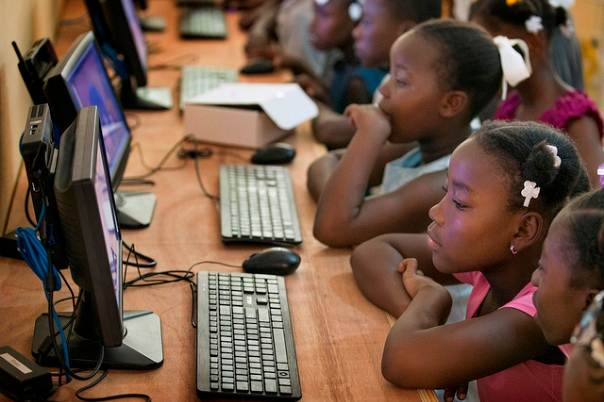 Children work in the computer lab at the Thomas Food Project in the town of Thomas, Haiti. Photo by Mike DuBose