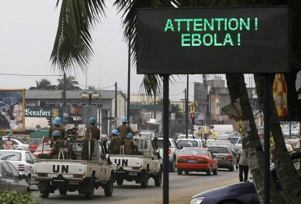 A U.N. convoy of soldiers passes a screen displaying a message on Ebola on a street in Abidjan, Ivory Coast, August 14, 2014. REUTERS/Luc Gnago