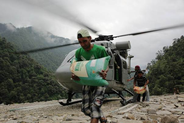 Indian villagers in Gaurikund town collect aid delivered by Indian Air Force helicopters, after floods and landslides  devastated the Indian state of Uttarakhand last month. Tens of thousands of people in remote Himalayan villages have been cut off by landslides, broken roads and bridges and are running in short supply of basic relief materials. Nita Bhalla /July 17, 2013