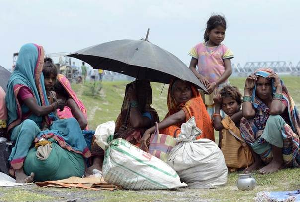 Villagers sit in a relief camp after being evacuated in Sipaul district in the eastern Indian state of Bihar, after a landslide in Nepal threatened them with floods. Picture August 3, 2014. REUTERS/Krishna Murari Kishan