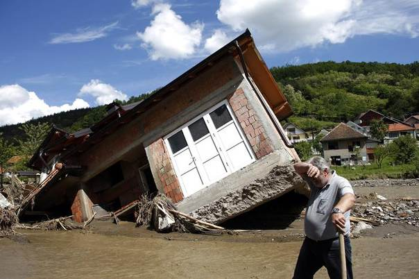 A man reacts near a house tilted by floods in the village of Krupanj, west from Belgrade, May 19, 2014.  REUTERS/Marko Djurica