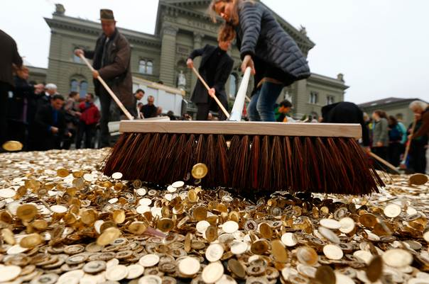 Committee members use brooms to spread out five cent coins over the Federal Square in Bern, Switzerland, on October 4, 2013. REUTERS/Denis Balibouse