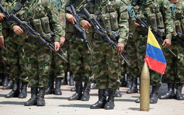 In a 2012 file photo, Colombian soldiers stand at attention next to their national flag during an inauguration ceremony for a new mobile brigade set up to fight against the Revolutionary Armed Forces of Colombia (FARC), in Florencia. REUTERS/John Vizcaino